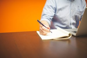 Man In A Blue Shirt Writing on a Pad of Paper with an Orange Background