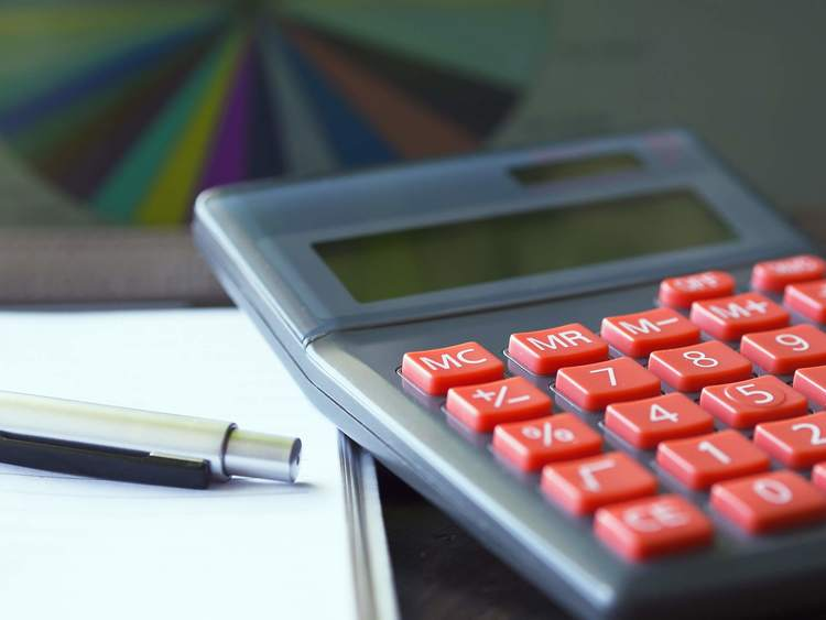 Grey Calculator with Red Buttons, Shown Alongside a Pen and Pad of Paper.